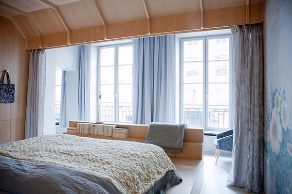 The bed is encased in a birchwood cocoon that looks out to grand French doors that open up to the city beyond. One wall is covered with a floral textile that brings out the calming shades of blue and gray in the space, and the bed area can be partitioned off with floor-to-ceiling curtains.
