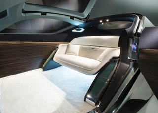 Interior details include an expansive OLED touch-screen, Macassar wood paneling, deep-pile ivory wool carpet, and a silky wool sofa. A luggage compartment is hidden near the front wheels.