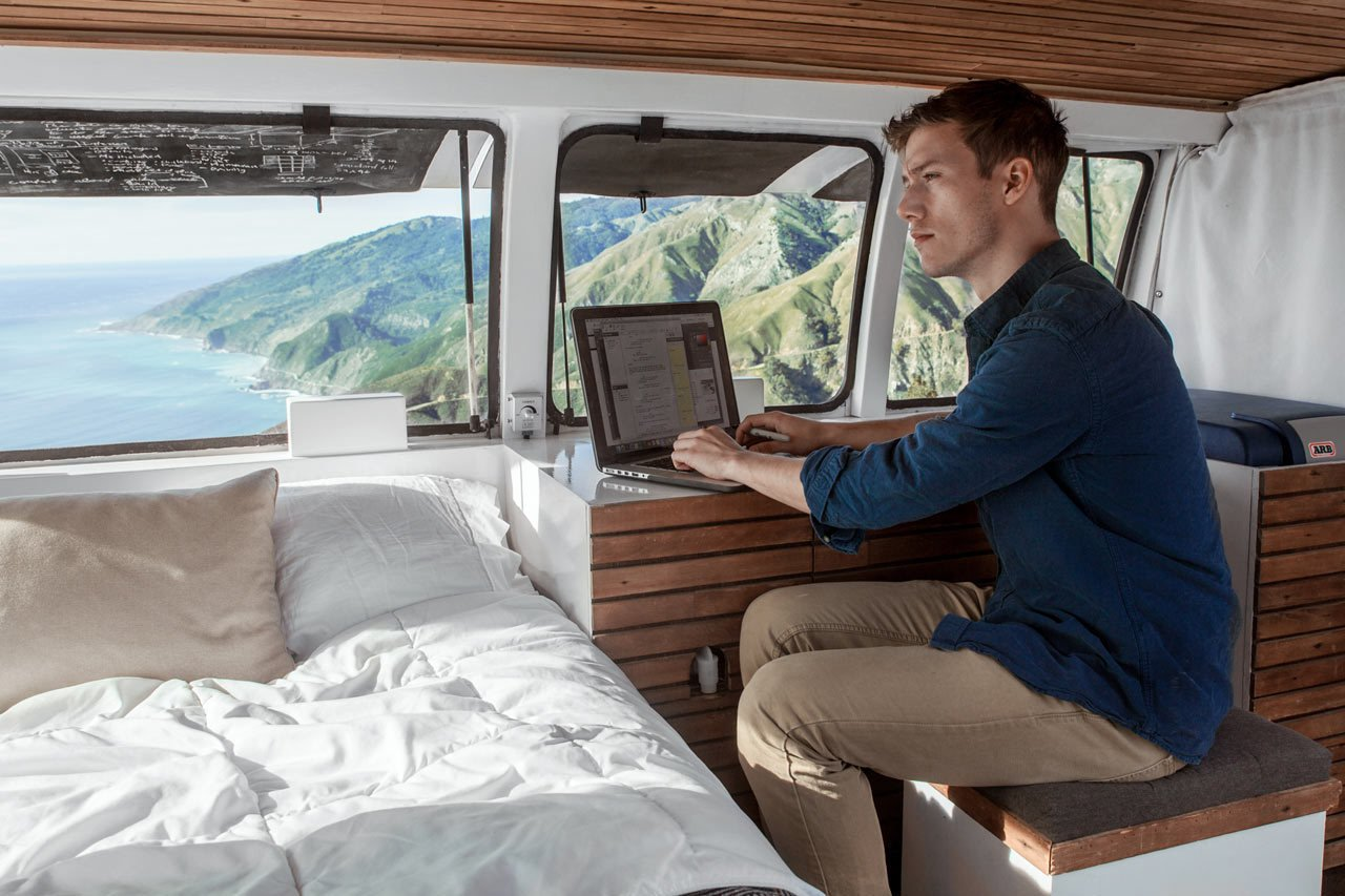 Cargo Van Mobile Studio bedroom with repurposed wood accents, Zach Both working at nightstand as a desk