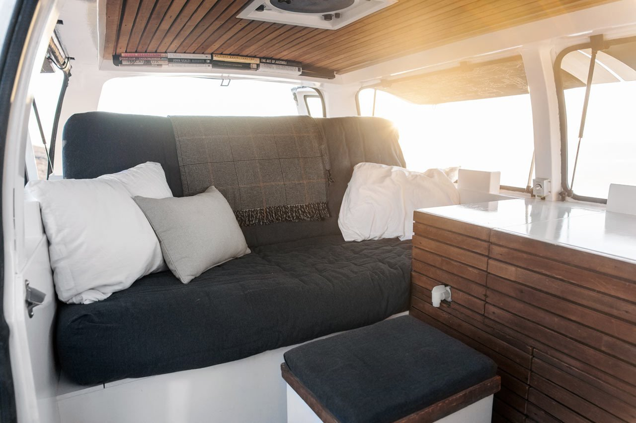Cargo Van Mobile Studio Living Area with cushioned bench and decorative pillows and throw