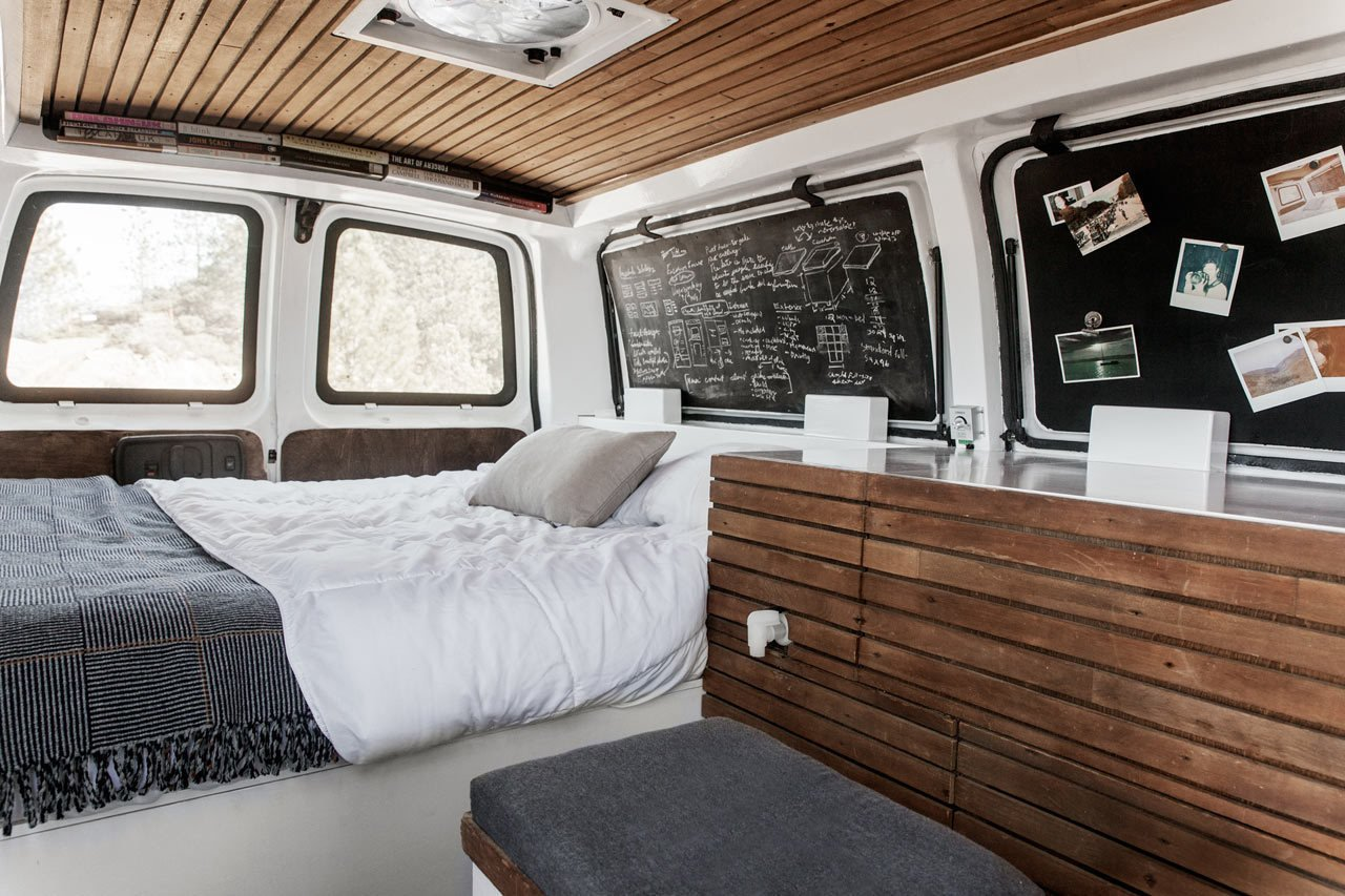 Cargo Van Mobile Studio bedroom with repurposed wood accents, window shutters folded in to show chalkboards
