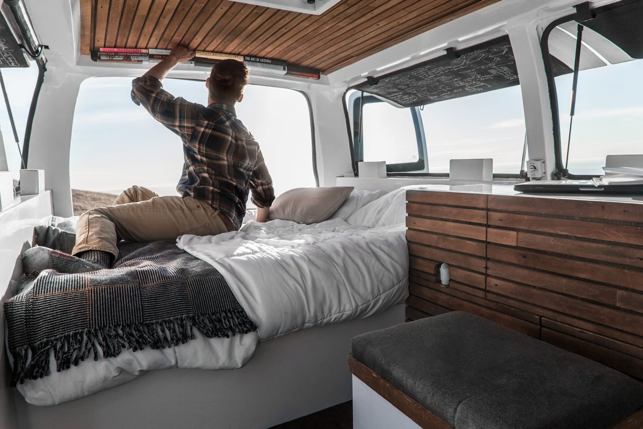 Cargo Van Mobile Studio bedroom with repurposed wood accents, Zach Both shown grabbing books from small shelf over bed