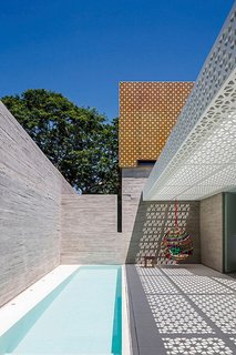 "Located in São Paulo, Brazil, this outdoor space designed by Figueroa Arq employs both poured-in-place concrete and perforated concrete blocks to produce a strong contrast between the white-and-orange lattice of the blocks and the solid walls of the gray concrete.  <span style=""color: rgb(204, 204, 204); font-size: 13px;"">Photo by Leonardo Finotti</span>"