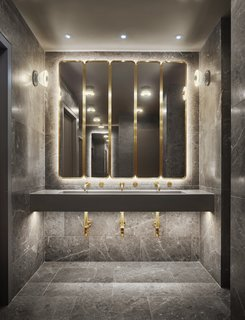 Porcelain tile, marble countertops, and brass trimmings give the in-room bathrooms a luxe feel.