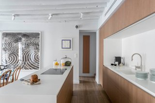 The subtle palette of white and wood is broken up by pops of color and pattern provided by the collection of the homeowner's artwork, which is strategically placed throughout the space for maximum impact.
