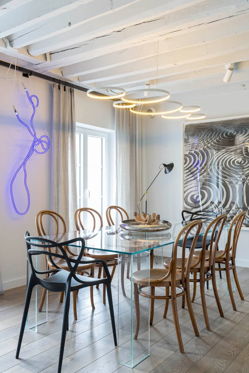 The dining room features a Glas Italia table that's paired with vintage Thonet chairs and two black Kartell chairs. The neon art is by Gun Gordillo and the piece on the right is by Alexandre Arrechea.  A Parisian Pied-À-Terre by Piret Johanson Studio #designmilk  Photo 6 of 20 in Pull Up a Chair in One of These 20 Modern Dining Rooms from A Parisian Pied-À-Terre by Piret Johanson Studio