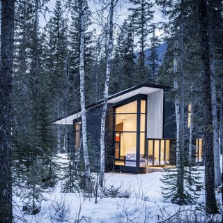 10 Modern Wintry Cabins We'd Be Happy to Hole Up In - Photo 7 of 10 - Form & Forest have designed the ultimate modern cabin that you can actually rent! Surrounded by wilderness, the retreat sits on the Blaeberry River near Golden, British Columbia with vaulted ceilings in the living room that afford incredible views of the forest, mountains, and river.