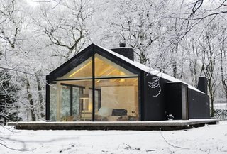 10 Modern Wintry Cabins We'd Be Happy to Hole Up In - Photo 8 of 10 - Oisterwijk Brouwhuis was designed by Bedaux de Brouwer Architecten and its finished structure resembles an elongated barn in the forests of Oisterwijk. The pitched roof makes way for a window wall that covers one entire end of cabin. The exterior is clad in black-stained wood, which matches the wooded forest and contrasts with the snow.