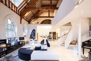 A Victorian-style church in London was converted by Gianna Camilotti Interiors into a modern home while keeping its historic charm. The outside may remain a traditional red brick, but the interior features white walls and floors, along with arched windows and wooden beams.