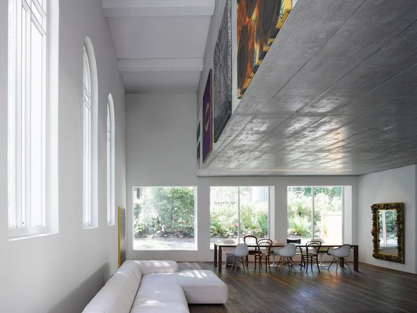 Located in Bern, Switzerland, the 1924 Luke Chapel went from rundown to two new modern homes by Morscher Architekten. To prevent covering the large church windows and to avoid adding support posts, the top apartment is suspended within a concrete box above. The box's facade was the perfect place to display artwork.