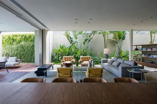 In order to give the clients what they wanted, the house takes up most of the property with no real yard. To bring in greenery, they lined the perimeter with plants. Large sliding glass doors open the living room up to the pool deck making those vertical gardens feel like they're indoors.
