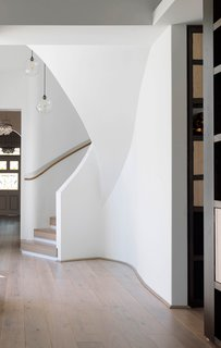An undulating spiral stair with a white railing on one side and a slim wooden handrail on the other connects the upper and lower floors of a renovated home in Australia. The bends of the railing mimic the curves of the building's exterior, and the wood handrail is recessed into the wall, tracing a path upwards.