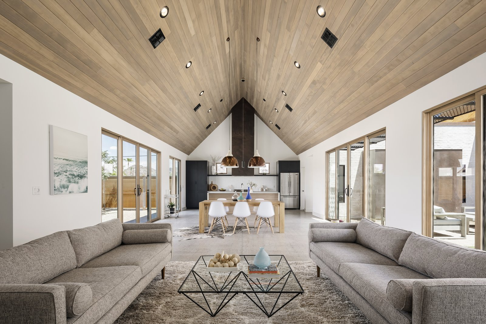 The great room is highlighted by a rusted metal custom hood at the end of the space, with courtyards on both sides Tagged: Living Room, Ceiling Lighting, Pendant Lighting, Coffee Tables, and Sofa.  Canal House by The Ranch Mine
