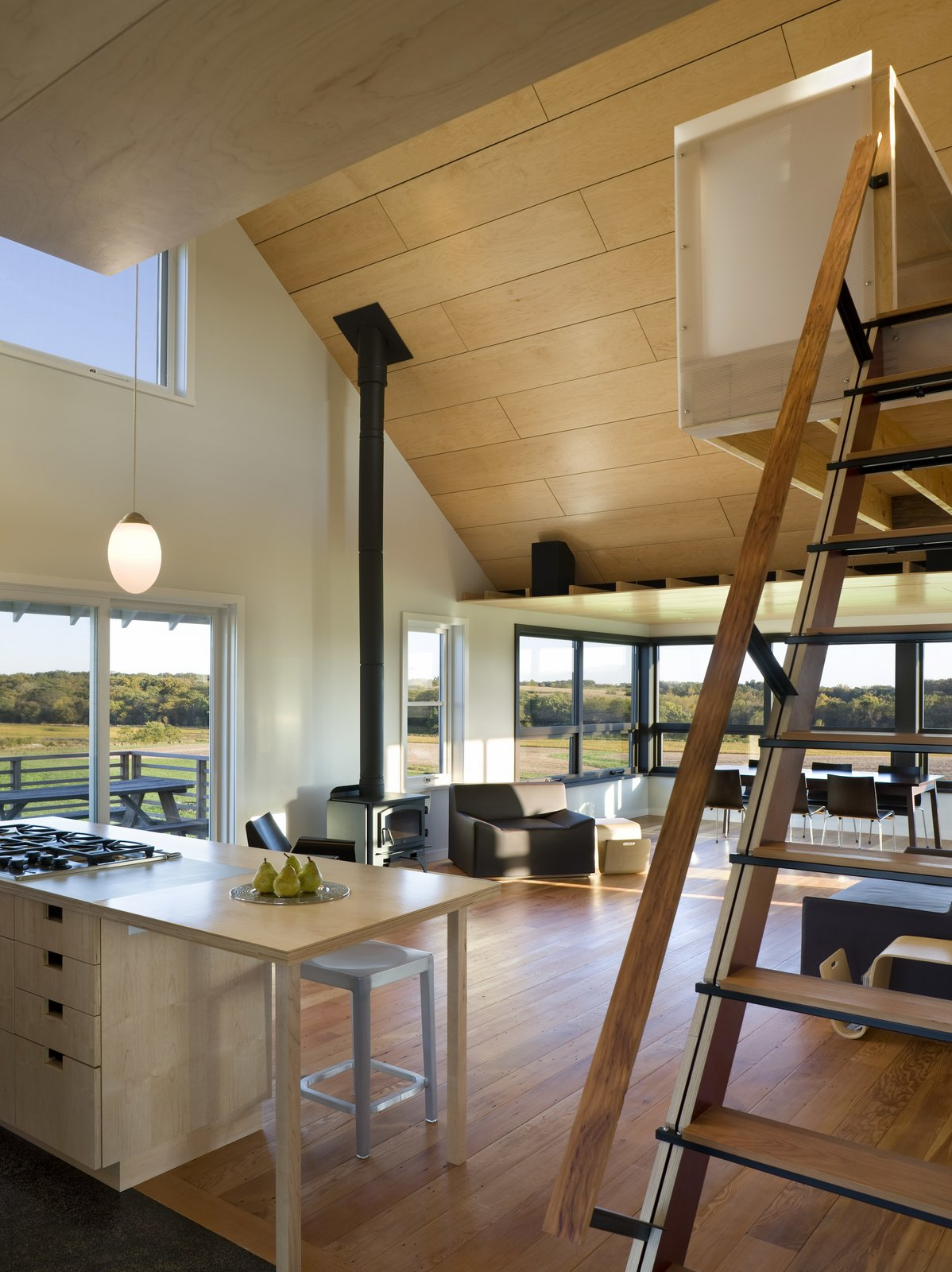 Sliding fabric panels allow the enclosed porch to be used for dining or overflow sleeping. A loft overlooking the main living space and views of the farm serves as office space.  Photo 2 of 10 in 10 Enclosed Porches That Are Put to Good Use