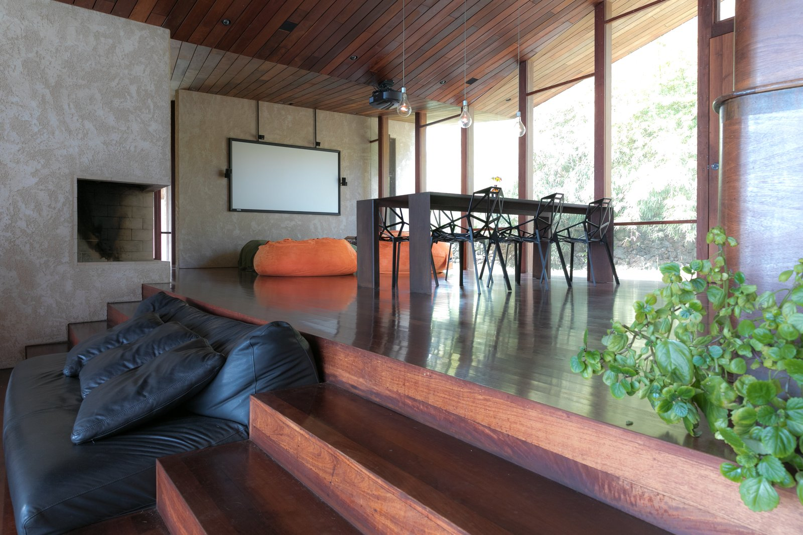 Living Room, Sofa, Dark Hardwood Floor, Bench, and Corner Fireplace  The Clifftop House by Modern on Maui - Liam Ball