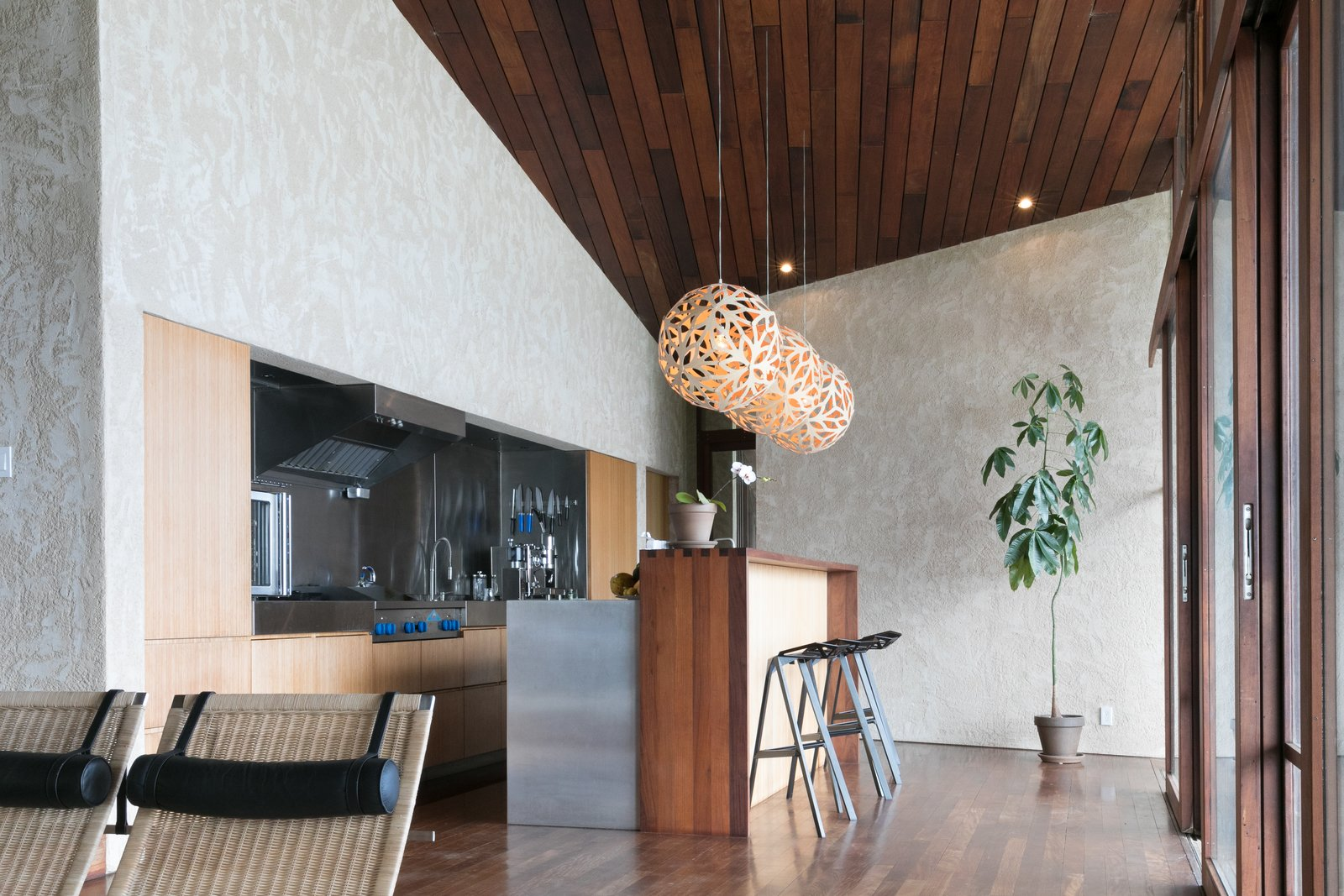 Kitchen, Wood Cabinet, Metal Counter, Dark Hardwood Floor, Metal Backsplashe, Pendant Lighting, and Refrigerator  The Clifftop House by Modern on Maui - Liam Ball