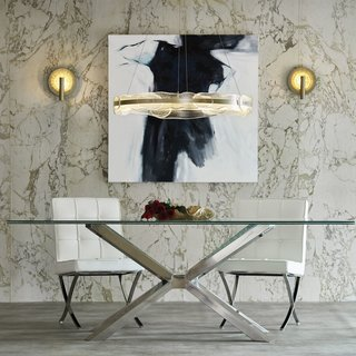 Glass-covered wall sconces illuminate either side of an art piece and act as a visual connector to the glass dining table and textured glass pendant over the table.