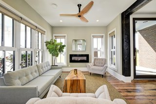 Windows and natural light surround the living room with a locally made Haiku Home ceiling fan.