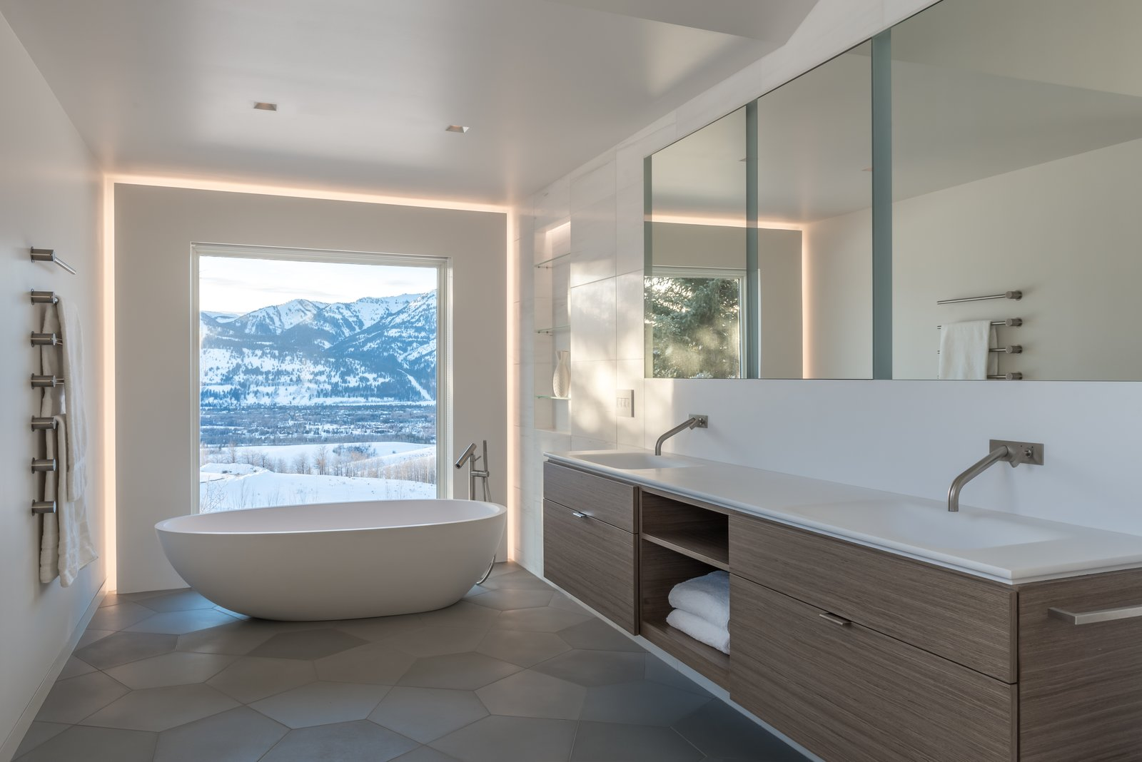 Previous master bathroom was divided into three separate spaces, with the mountain view terminating in a closet.  The walls were removed to open views to the west and create one large space.  Custom pentagon shaped concrete tiles compliment the Eco-Wood veneer floating vanity.  San Francisco Meets Jackson Hole in a Modern Renovation by Carney Logan Burke Architects
