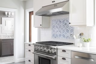 A custom backsplash was designed using Ann Sacks tile which compliments the marble countertop and accentuates the Wolf range.