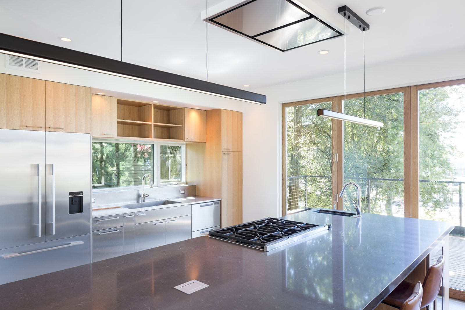 Kitchen, Engineered Quartz Counter, Wood Cabinet, Light Hardwood Floor, Ceiling Lighting, Pendant Lighting, Refrigerator, Range, Range Hood, Dishwasher, Beverage Center, and Undermount Sink  Contemporary Home With Chef's Kitchen by Model Remodel