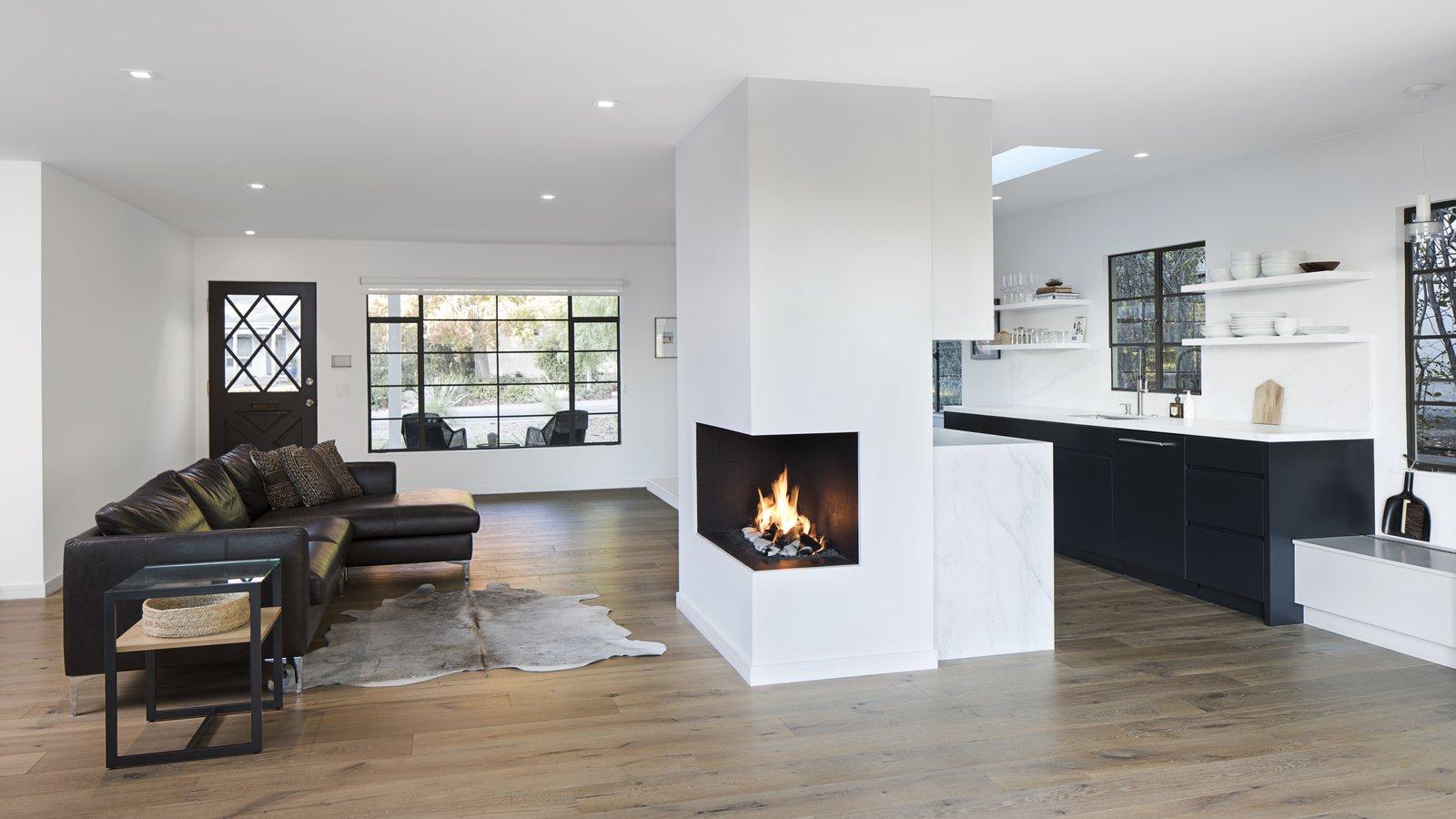 Living Room, Ceiling Lighting, Light Hardwood Floor, Sofa, and Corner Fireplace  Vista De la Cumbra
