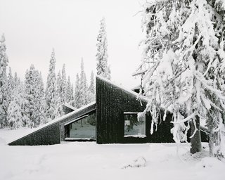 Architect Håkon Matre Aasarød, partner at Oslo-based studio Vardehaugen Architects, led the design of Cabin Vindheim, situated deep in the forest in the alpine landscape near Lillehammer, Norway . The cabin's concept was simple: To create a cabin that is small and sparse yet spatially rich. The 55-quare-meter (592-square-foot) cabin, commissioned by a private client and completed in 2016, comprises a large living room, bedroom, ski room, and small annex with a utility room. It functions off the water and electricity grids.