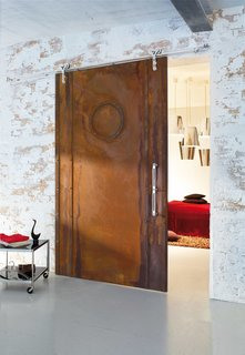 Wood barn door utilizing a modern barn door hardware as an entrace to a bedroom.