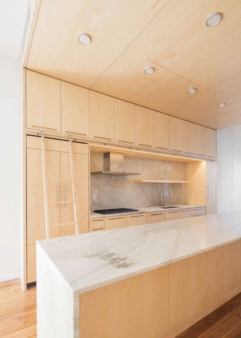 Kitchen, Range, Range Hood, Marble Counter, Medium Hardwood Floor, Marble Backsplashe, and Wood Cabinet  Wayne Street Row House by Jeff Jordan Architects
