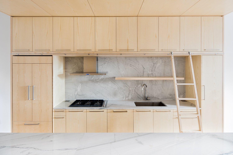 Kitchen, Wood Cabinet, Range, Range Hood, Marble Counter, and Marble Backsplashe  Wayne Street Row House by Jeff Jordan Architects
