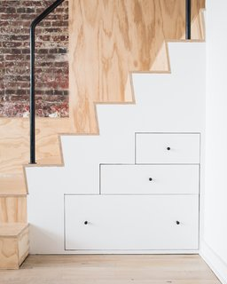 In the renovation of this former industrial loft for an artist into a studio and living space, built-in drawers under a plywood staircase create visual drama as well as practical storage. By using drawers instead of cabinets, the lower portion of the custom solution is easier to access than if it were cabinets on hinges, and the geometry of the drawers mimics the stair tread.