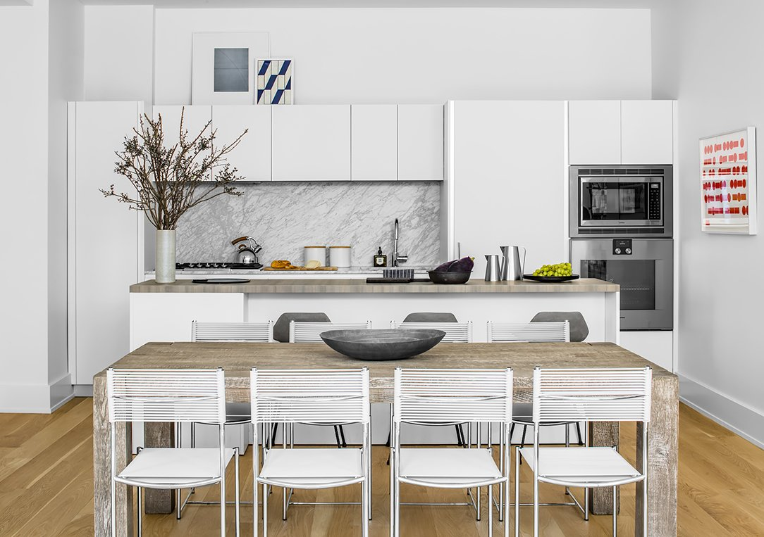 Kitchen, White, Range, Light Hardwood, Wall Oven, Marble, Undermount, and Microwave  Best Kitchen Microwave Marble Photos from This New York Apartment Is What Dreams Are Made Of
