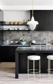 In this kitchen by DISC Interiors, the stark black cabinets and kitchen island are offset by light whitewashed floors and white-and-brass accents. To finish off the look, a patterned ceramic tile backsplash packs a punch.