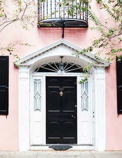 Knock, knock. Who's there? A fresh front door color combination. It doesn't get more classic that a jet-black front door, but in this case, the blush walls give the traditional shade a trendy new twist.