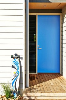 When you have a clear favorite color, it's a no-brainer to paint your front door. And it's hard to beat the cool factor that comes from a vibrant blue front door like this one. The shade is a modern mid-blue that's not too light and not too dark. Best of all, it connects back to the accent colors in other favorite items like the owner's longboard.