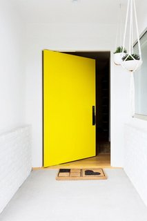 This vibrant, happy shade of yellow invites the sunshine (and sunny vibes) in. That's what makes yellow one of my favorite colors. Accessorized with a simple welcome mat and a few hanging plants, this bright door only requires minimal décor to make a big opening statement.