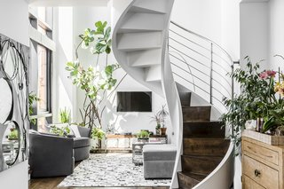 """Says the architect, James Wagman Architect, """"Our client, a sculptor, also required the additional space to accommodate her artwork. A custom helix staircase became the central focus with various upgrades throughout. Special attention was paid to decorative details and finishes to complement her metal sculpture decorating her home."""""""