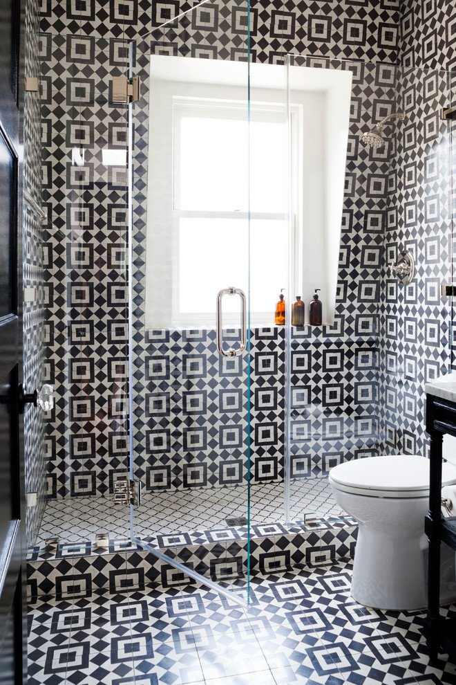Monochrome tiles define the shape of this transparent bathroom shower. Designer Stacy Zarin Goldberg of Breeze Giannasio Interiors filled this space with thick visual texture and functional designation between the shower floor and the rest of the room. Tagged: Bath Room, One Piece Toilet, Ceramic Tile Wall, Enclosed Shower, and Ceramic Tile Floor.  Photo 19 of 20 in 20 Bathrooms With Transformative Tiles