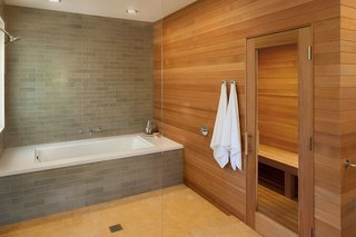 Natural wood warms the stone palette of this master bathroom designed by Mark Reilly Architecture.