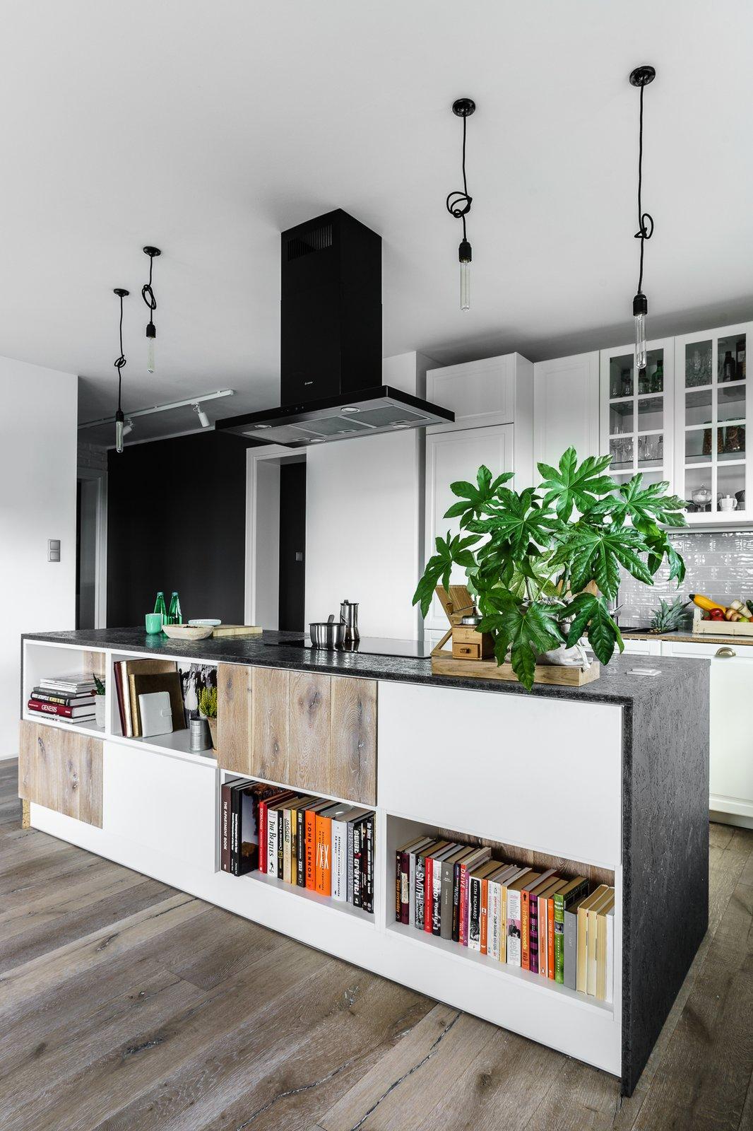 Kitchen, White Cabinet, Medium Hardwood Floor, Granite Counter, Glass Tile Backsplashe, Subway Tile Backsplashe, Pendant Lighting, Range Hood, and Cooktops  Loft in Poland