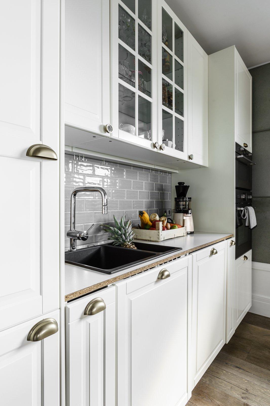 Tagged: Kitchen, Subway Tile Backsplashe, Glass Tile Backsplashe, White Cabinet, and Drop In Sink.  Loft in Poland