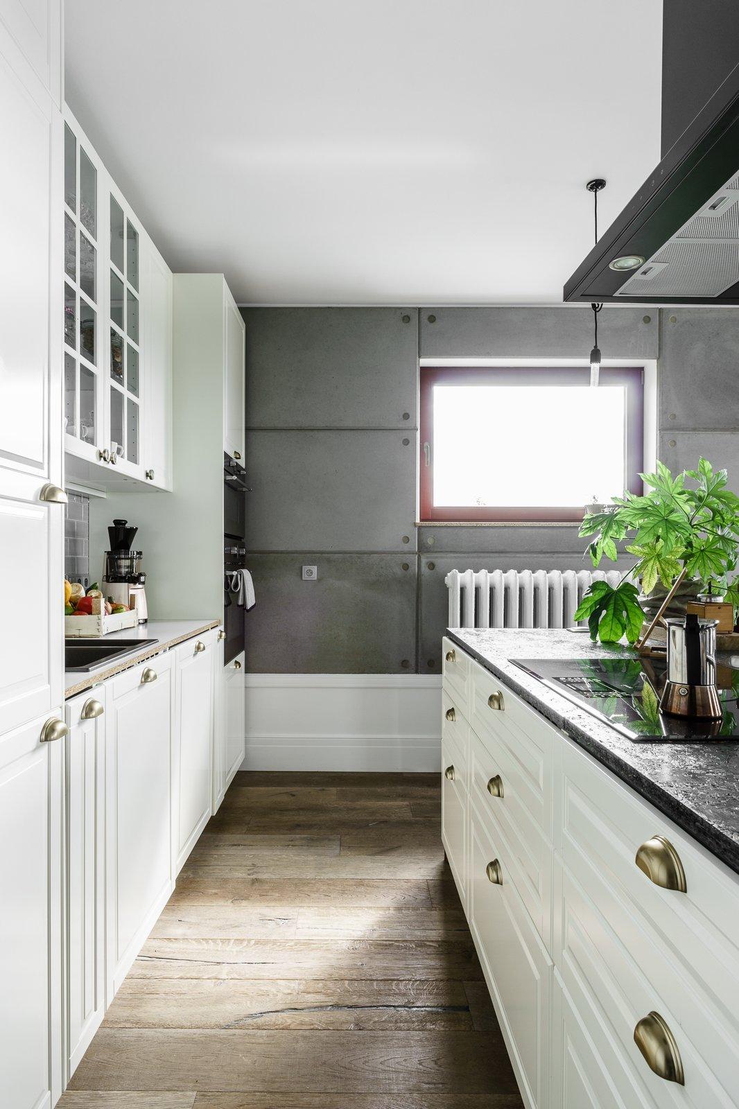 Kitchen, Cooktops, White Cabinet, Granite Counter, Medium Hardwood Floor, Range Hood, and Drop In Sink  Loft in Poland