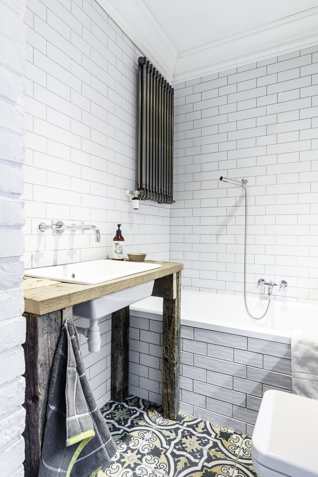 Bath Room, Pedestal Sink, Soaking Tub, Wood Counter, Drop In Sink, Subway Tile Wall, and Ceramic Tile Wall  Loft in Poland