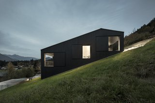 An Austrian vacation home's design references its mountainside setting and expansive views across the valley, and is an exercise in contrasts: its exterior is painted black, but its interiors are light-filled and clad in natural wood.