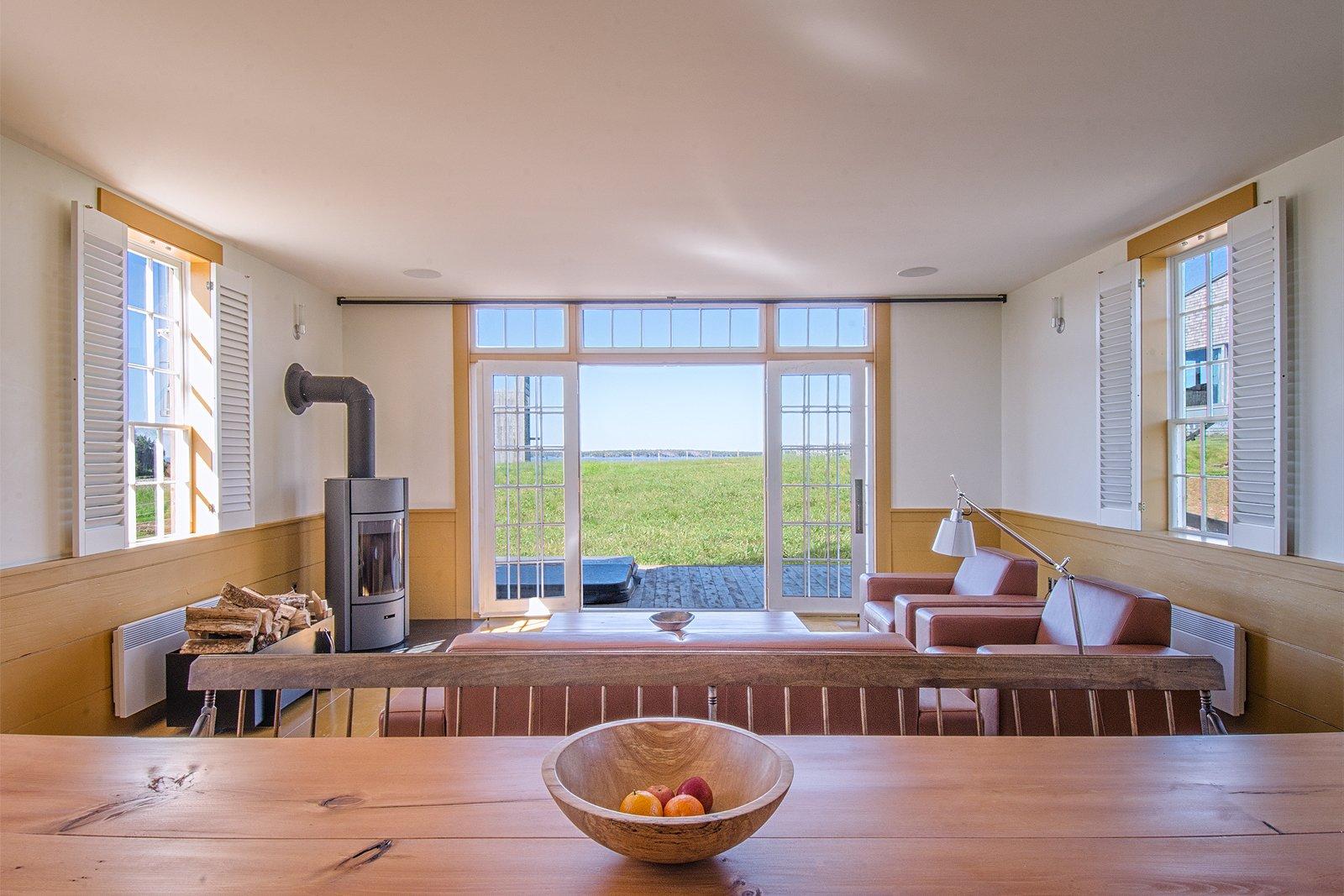 Living Room, Light Hardwood Floor, Sofa, Corner Fireplace, Wood Burning Fireplace, and Recessed Lighting  Schoolhouse