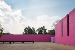 A Cuadra San Cristóbal courtyard surrounded by vibrant pink walls.
