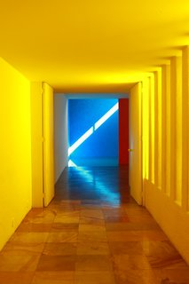 Only one wall in the pool corridor at Casa Gilardi is yellow; the other is white. Light enters via the adjacent courtyard, resulting in a warm glow.