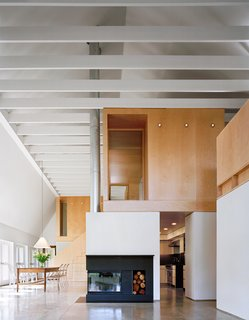 Simple and durable, yet elegant materials such as polished concrete, second-grade oak flooring, and maple plywood are used throughout. Interior and exterior connect visually through a wall of glass doors to the garden and fields beyond.