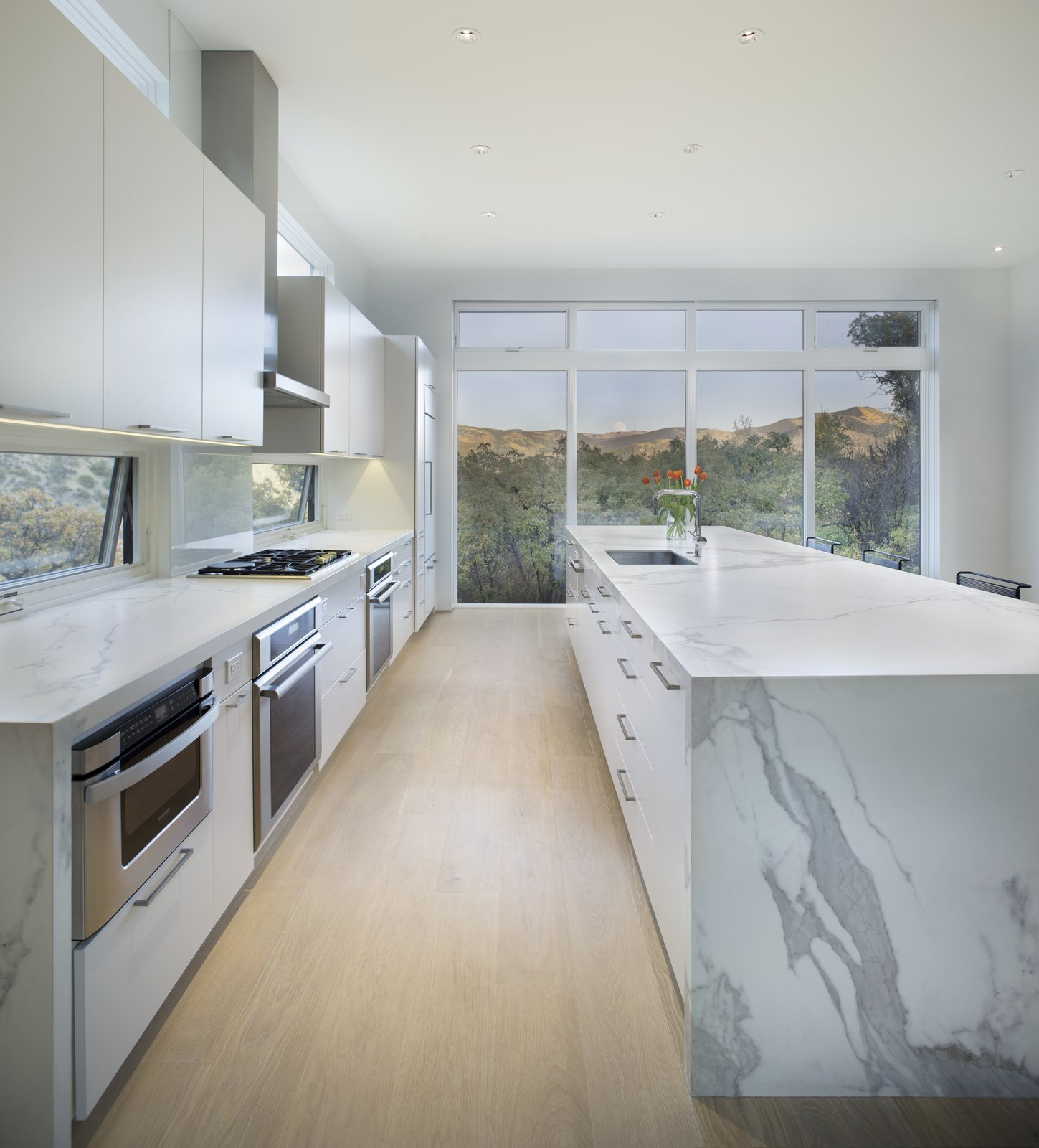 Kitchen, Marble Counter, White Cabinet, and Light Hardwood Floor  Black Magic by rowland + broughton