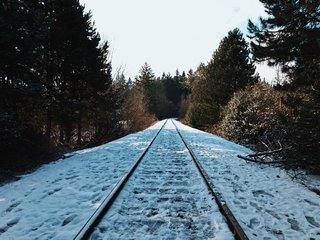 Icy foot tracks mark this snow-pelted section of railroad track.